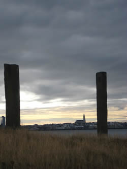 View of Reykjavík (and Hallgrímskirkja) from the West island of Viðey. The two basalt pillars in the foreground are part of Richard Serra's installation '�fangar,' ('Milestones') which 'frame' various landmarks and sites around the islan