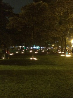 Families lighting candles in the park to celebrate Día de las Velitas