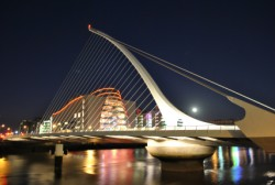 The iconic Samuel Beckett Bridge backlit by the full moon and the Convention Centre